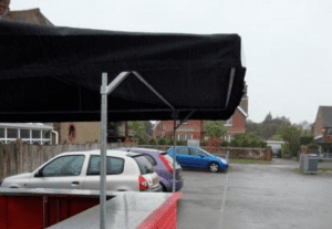Big kahuna hut with black roof overhang in a car park