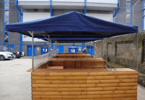 Big kahuna wooden hut with dark blue roof in a car park