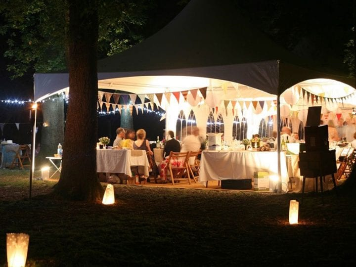 People sitting inside a 6m Pagoda Marquee at night time
